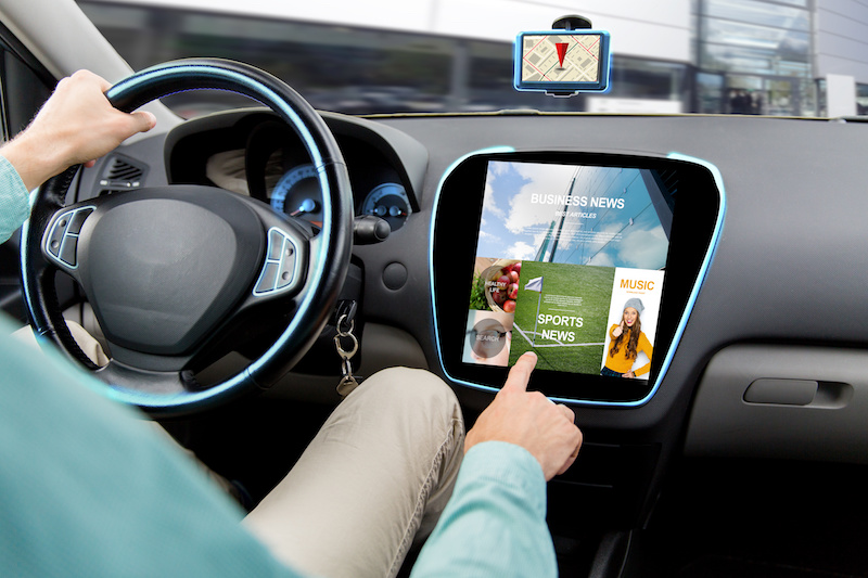 transport, road trip, technology, media and people concept - close up of man driving car and using news application on computer